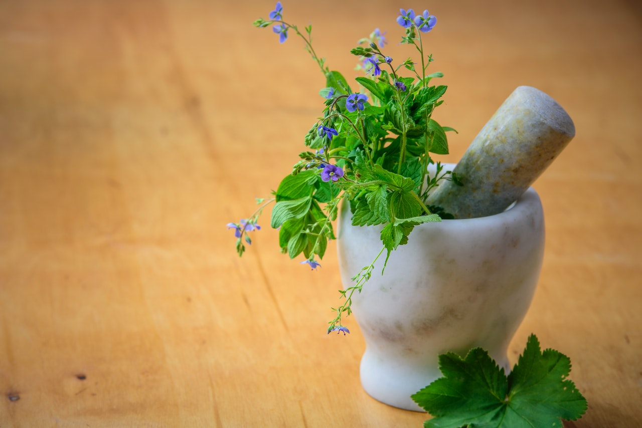a mortar and pestle with fresh herbs